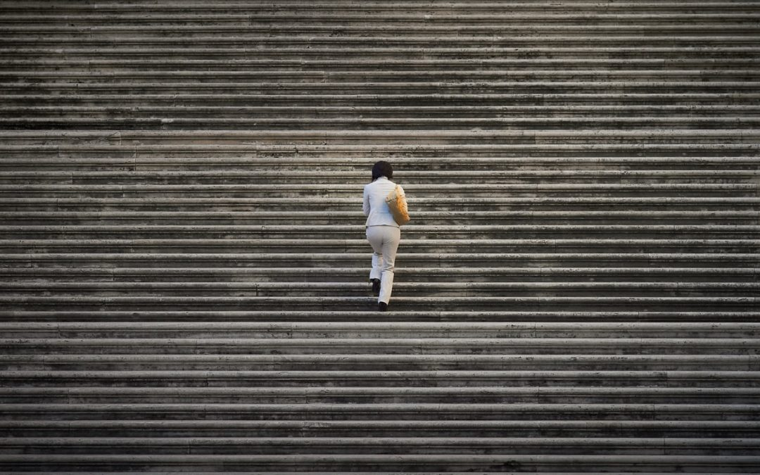 20 Companies Setting the Standard for Leadership During Crisis | Talencio | Woman Walking Up a Flight of Stairs Alone